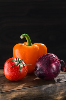 Fresh vegetables onion tomato and peppers on a dark wooden board