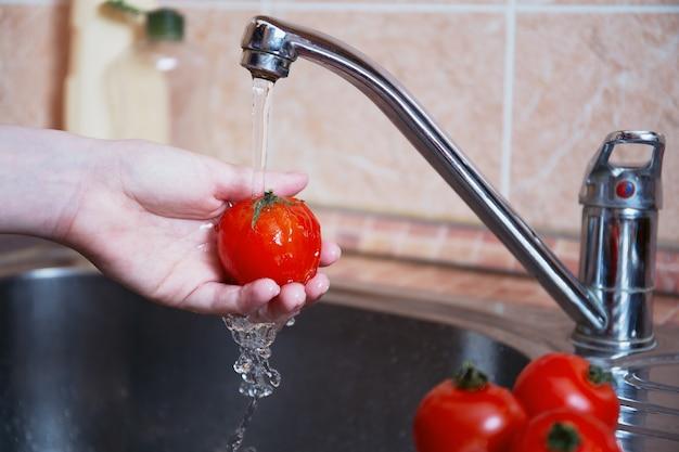 흐르는 물에 신선한 야채나 즙이 많은 토마토. 여성의 손은 신선한 야채를 씻습니다.