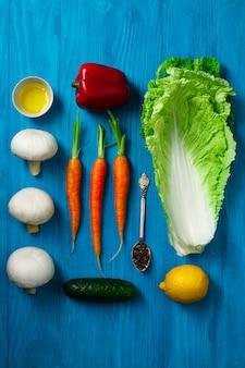 青い木製の表面上の新鮮な野菜