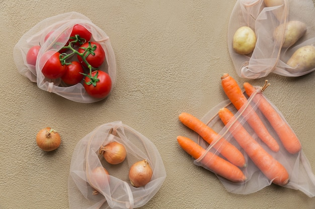플라스틱 포장에서 졸라 매는 끈이 거부 된 재사용 가능한 메시 백에 포장 된 신선한 야채