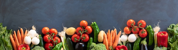 Fresh vegetables panorama on dark rustic wooden background. top view. copy space