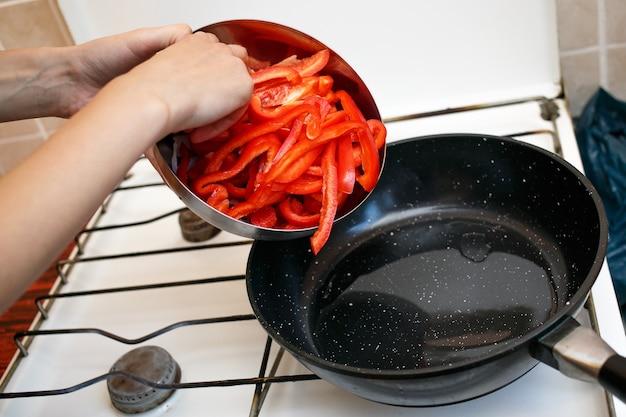 프라이팬에 신선한 야채, 고추 및 양파, 가정 소비에트 연방 주방에서 음식 요리