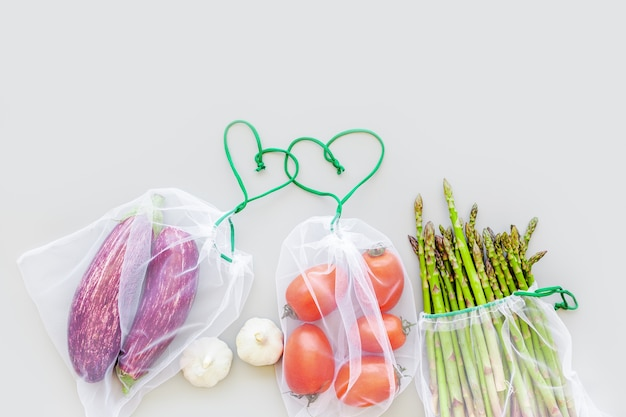 Fresh vegetables in reusable produce shopping bags
