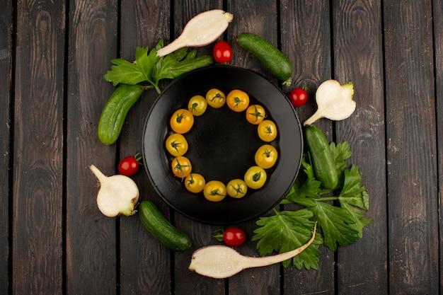 Pomodori gialli maturi degli ortaggi freschi e altre verdure variopinte su un di legno