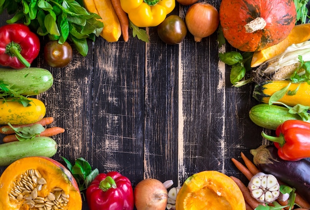 Fresh vegetables on a rustic dark textured table. autumn background