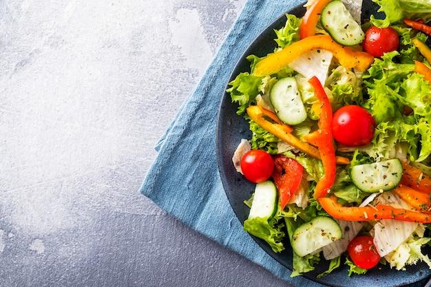 皿に新鮮な野菜のサラダ。健康とダイエット食品のコンセプト。テキスト用のスペース、上面図