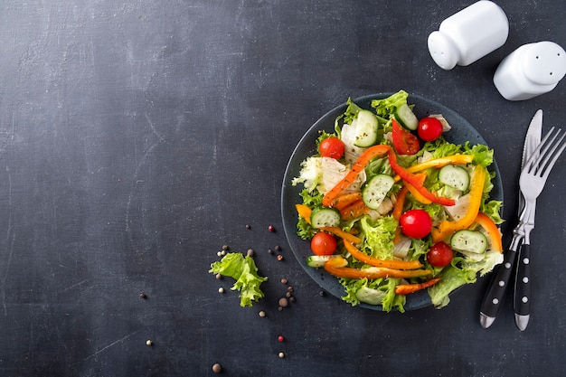 皿に新鮮な野菜のサラダ。健康とダイエット食品のコンセプト。上面図、テキストスペース