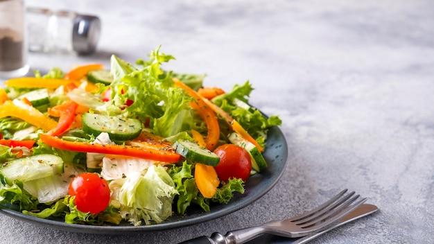 新鮮な野菜のサラダを皿に盛り付けます。健康食品のコンセプト。