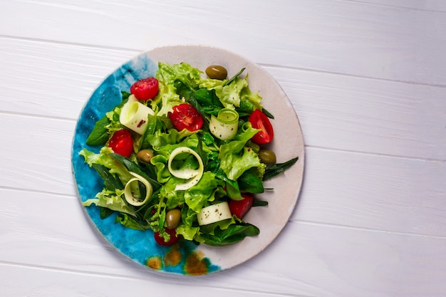 Fresh vegetables salad with greens and tomatoes