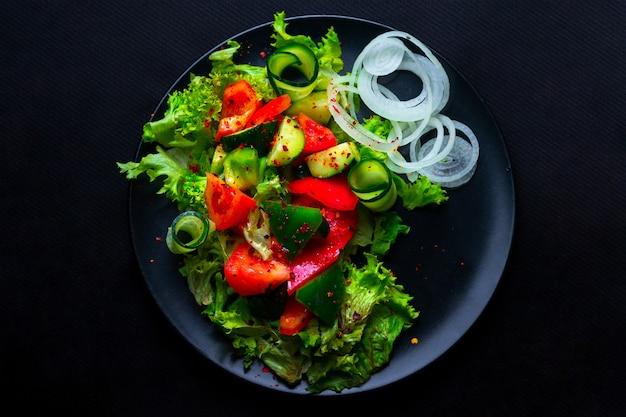 Салат из свежих овощей с фиолетовой капустой, белокочанной капустой, салатом, морковью в темной глиняной миске на черном фоне. вид сверху
