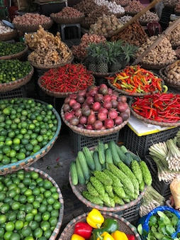 Fresh vegetables for sale at street food market in the old town of hanoi, vietnam. garlic, lemon, ananas, onions, peper, red chillies, carots