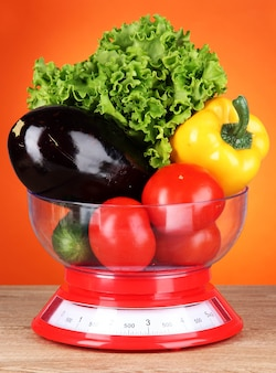 Fresh vegetables in scales on table on orange