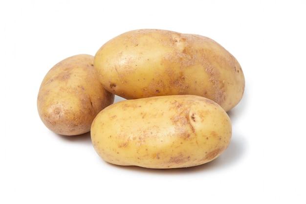 Свежие овощи. несколько клубней картошки на стене изолированной белизной. желтый картофель.