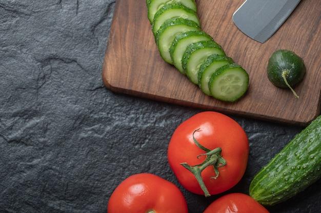 젖은 블랙 테이블에 신선한 야채 슬라이스. 토마토와 오이 조각. 고품질 사진