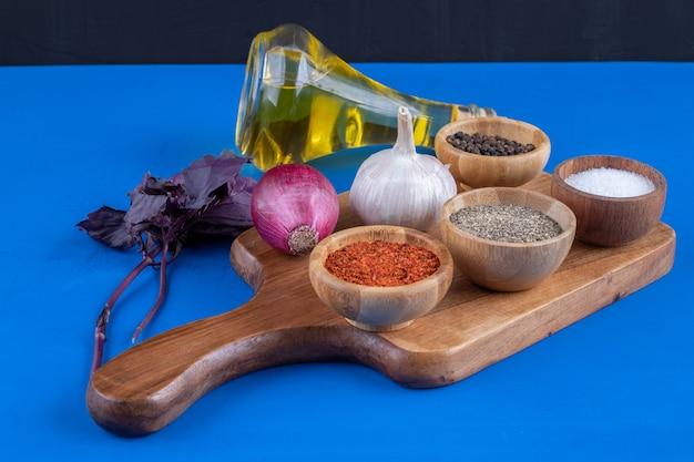 Свежие овощи, специи и бутылка оливкового масла на деревянной доске
