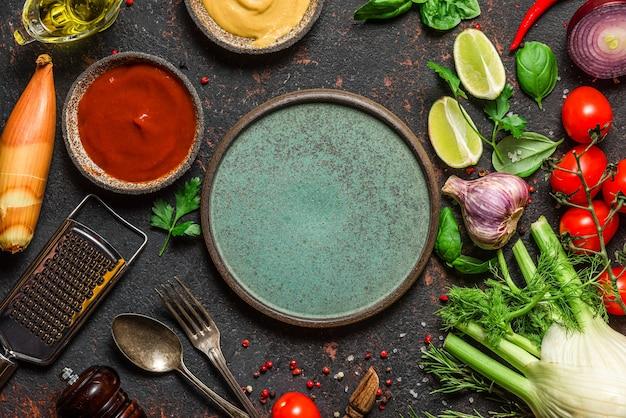 新鮮な野菜、スパイス、ハーブ、プレート、カトラリー、調理器具、黒いテーブル