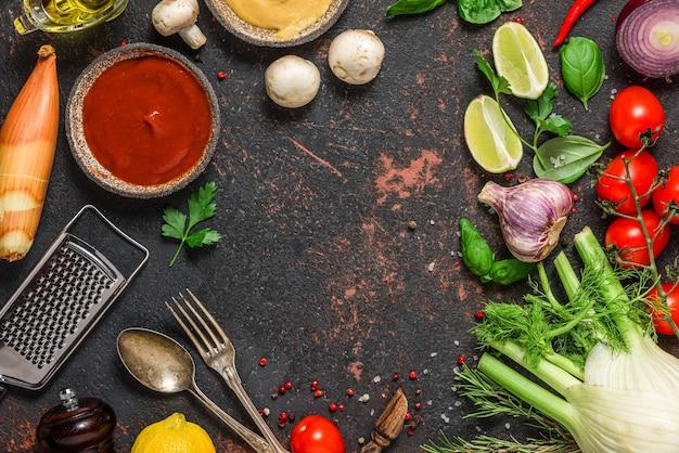 新鮮な野菜、スパイス、ハーブ、ソース、カトラリー、調理器具、黒い石の表面