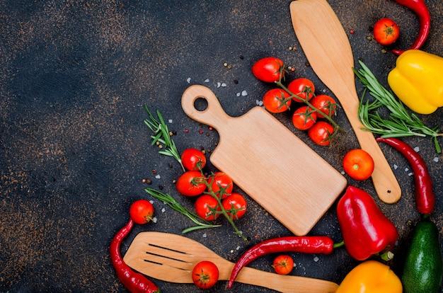 新鮮な野菜、スパイス、ハーブ健康的な料理や、テキスト用のスペースのある暗い素朴な背景でのサラダ作りの材料。上面図