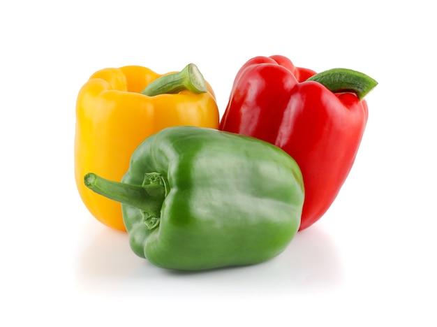 Свежие овощи три сладких красных, желтых, зеленых перца изолированы
