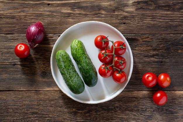 素朴なテーブルの上に新鮮な野菜のトマトとキュウリ