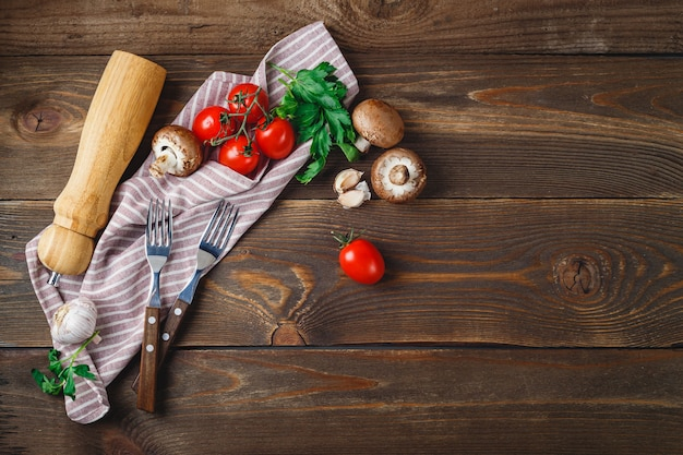 新鮮な野菜-トマト、ニンニク、シャンピニオン、パセリ、ペッパーシェーカー、フォーク、木製の背景にナプキン。テキストの場所。上面図