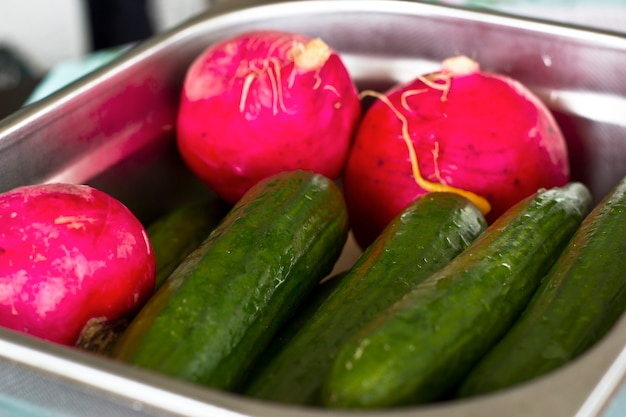 Fresh vegetables turnips and cucumbers in a metal tray