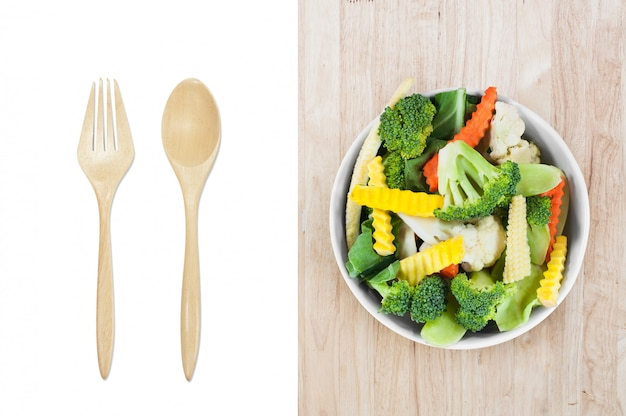 Fresh vegetables in white bowl with wooden spoon and fork isolated on white background