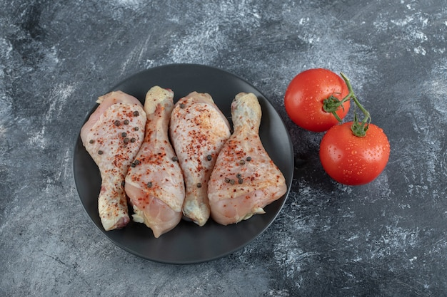 灰色の背景に鶏のドラムスティックと新鮮な野菜。