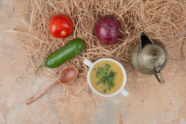 Fresh vegetables with delicious soup on marble surface