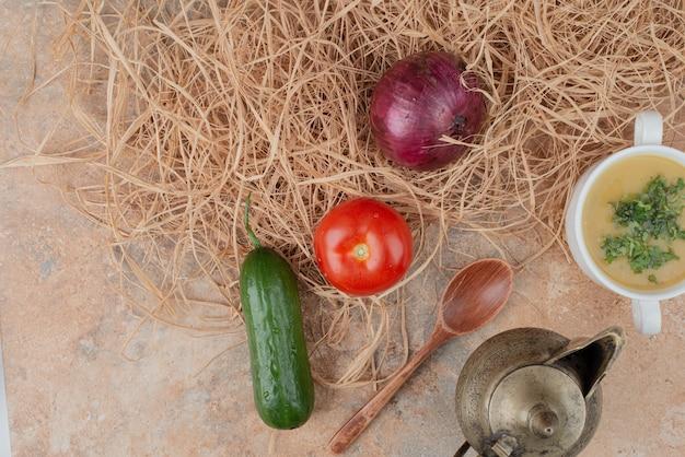 Свежие овощи с вкусным супом на мраморной поверхности