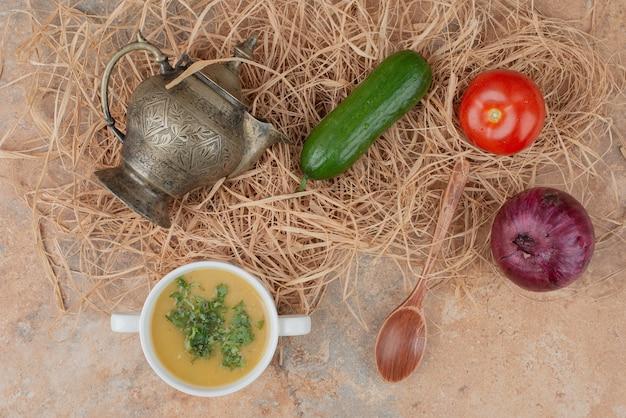 Свежие овощи с вкусным супом на мраморе