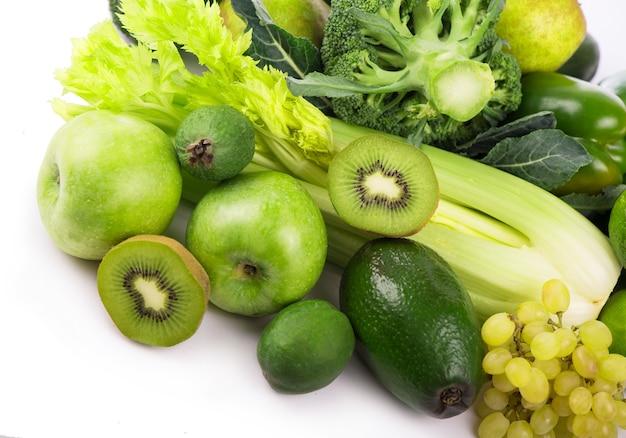 Свежие овощи с листьями - киви, виноград, яблоки и ломтики, огурцы, кабачки, брокколи, капуста и зелень, изолированные на белом фоне.