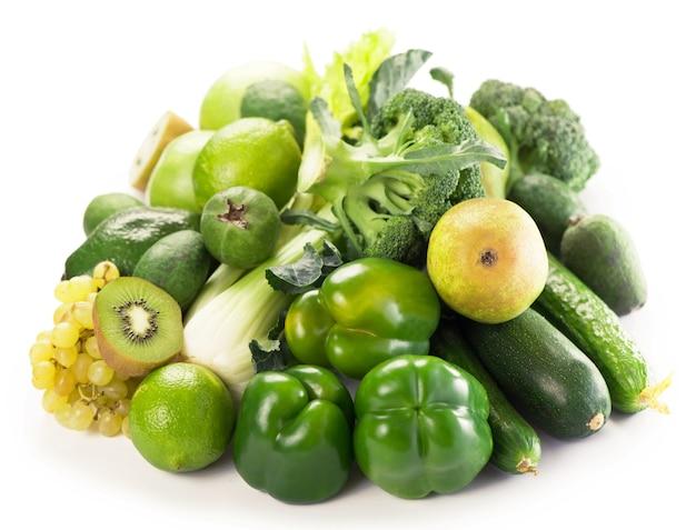 Свежие овощи с листьями - киви, виноград, яблоки и ломтики, огурцы, кабачки, брокколи, капуста и зелень, изолированные на белой поверхности