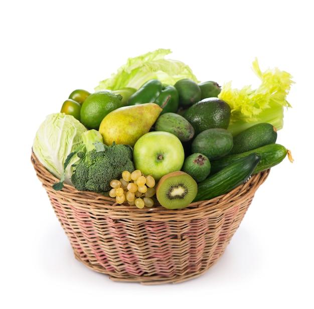 Свежие овощи с листьями киви, виноград, яблоки и ломтики огурцов, кабачков, брокколи
