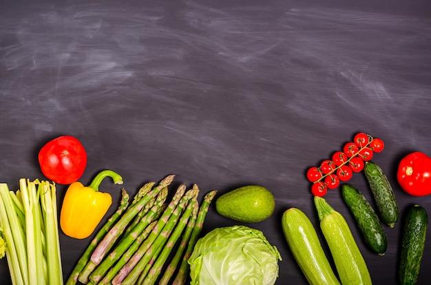 黒の背景にテキストの場所と新鮮な野菜。季節の春の収穫。フラットレイ、コピースペース。健康食品のコンセプト。上から見る