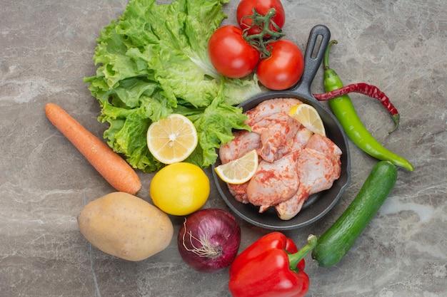 Свежие овощи с сырой курицей на мраморном фоне. фото высокого качества