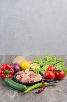 대리석 바탕에 원시 닭고기와 신선한 야채