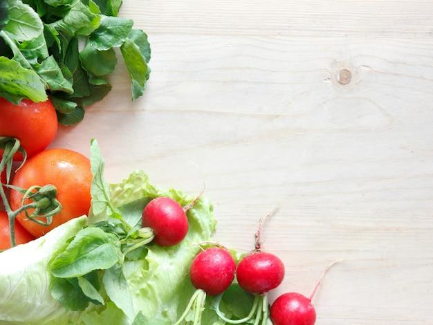 Fresh vegetables on a wooden board - radish, lettuce, arugula, tomatoes