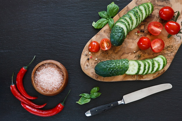 Fresh vegetables on wooden cutting board with knife on black concreted background
