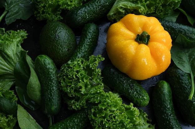黒の背景に新鮮な野菜、黄色のピーマン、キュウリ、サラダ。