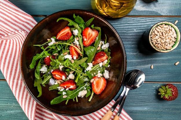 Свежий вегетарианский диетический салат с клубникой, арагулой и сыром. предпосылка рецепта еды. закройте вверх. вид сверху.
