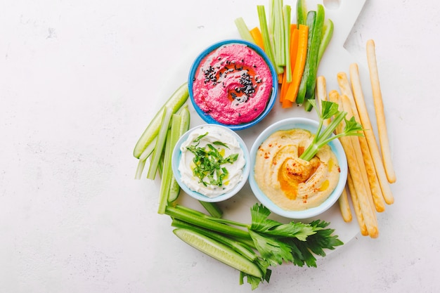 Fresh vegetarian dips in small bowls on table
