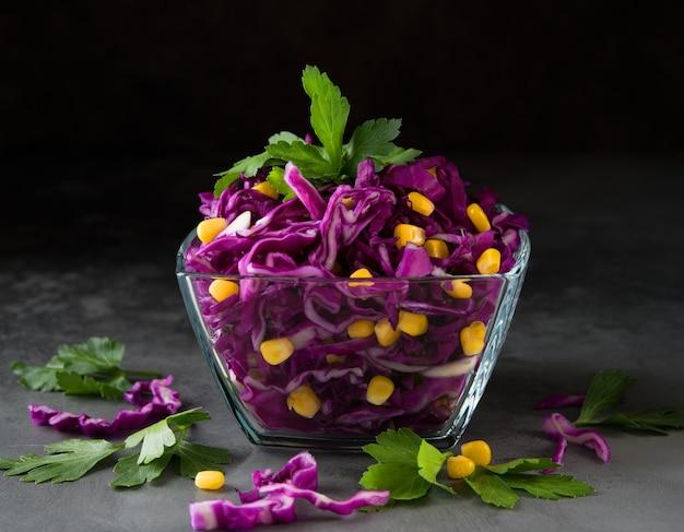 Свежий вегетарианский салат с красной капустой и кукурузой на темно-серой поверхности
