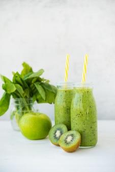 緑の果物と野菜のガラス瓶の中の新鮮なベジタリアンスムージードリンク。スペースのコピー