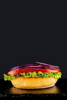 Fresh vegetarian tasty burger on a black background. making a burguer in stages