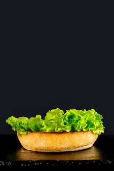 Fresh vegetarian tasty burger on a black background. making a burguer in stages
