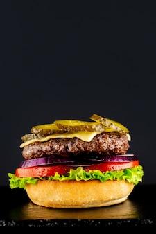Свежий вегетарианский вкусный бургер на черном фоне. делаем бургер поэтапно