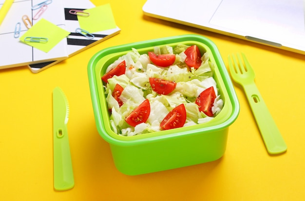 Fresh vegeterian salad in green lunch box with plastic fork and knife at office workplace.close up of healthy snack in plastic container.healthy food concept.top view, flat lay,yellow background.