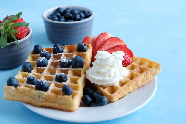 Fresh viennese homemade waffles with bio strawberries and blueberries and whipped cream on a blue background.