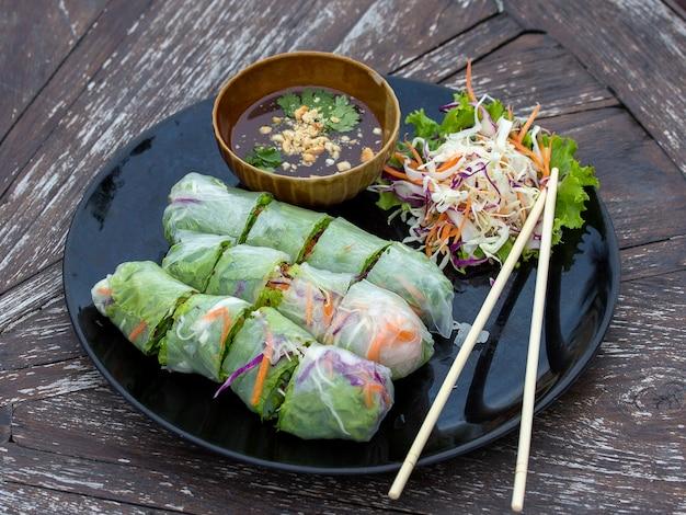 新鮮なベトナムの春巻きをサラダと一緒に皿に盛り付けます